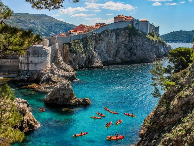 Uitzicht op de stadsmuur van Dubrovnik en varende mensen.