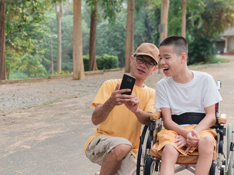 Kind in rolstoel bekijkt foto met vader